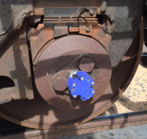 RailSafe RotoSense sensor module (blue) mounted on train axle hub